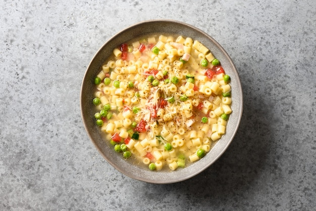 Zelfgemaakte groentesoep van erwten, tomaten, ditalini-soepdeegwaren op grijze lijst.