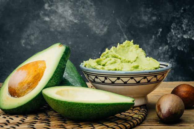 Zelfgemaakte guacamole en rauwe avocado's op een houten tafel