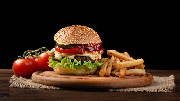 Zelfgemaakte hamburger close-up met rundvlees, tomaat, sla, kaas en frietjes op snijplank. fastfood op donkere achtergrond.