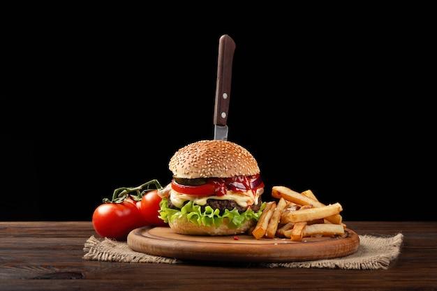 Zelfgemaakte hamburger close-up met rundvlees, tomaat, sla, kaas en frietjes op snijplank. in de burger stak een mes