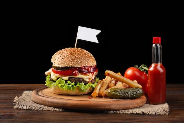 Zelfgemaakte hamburger close-up met rundvlees, tomaat, sla, kaas en frietjes op snijplank.