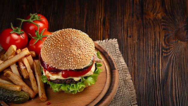 Zelfgemaakte hamburger close-up met rundvlees, tomaat, sla, kaas en frietjes op snijplank