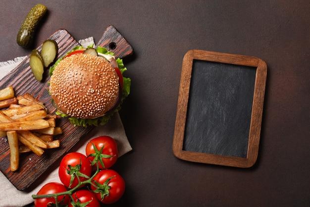Zelfgemaakte hamburger met ingrediënten rundvlees, tomaten, sla, kaas, ui, komkommers en frietjes op snijplank en roestige achtergrond