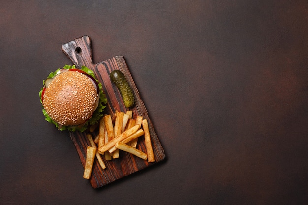 Zelfgemaakte hamburger met ingrediënten rundvlees, tomaten, sla, kaas, ui, komkommers en frietjes