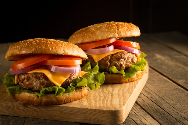 Zelfgemaakte hamburger met rundvlees, ui, tomaat, sla en kaas. verse hamburger close-up op houten rustieke tafel met frietjes, bier en chips. cheeseburger.
