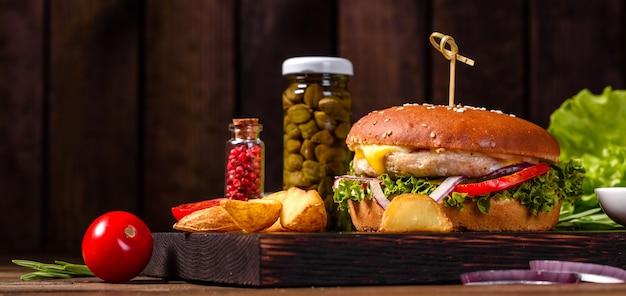 Zelfgemaakte hamburger met sla en kaas. close-up van zelfgemaakte smakelijke hamburgers op houten tafel