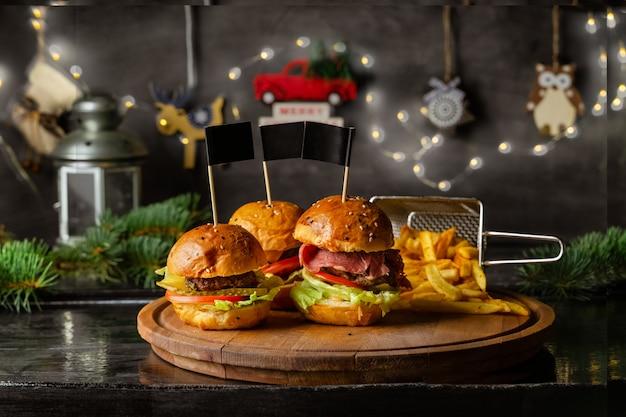 Zelfgemaakte hamburgers en frietjes op een houten bord met kerst decor aan de muur, close-up weergave