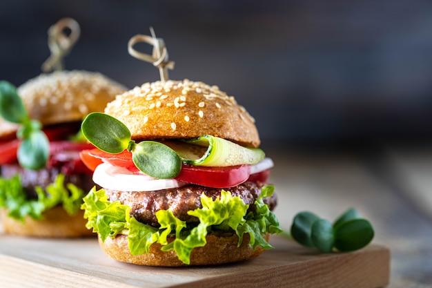 Zelfgemaakte hamburgers met kotelet, verse sla, tomaten, uien op een houten tafel. kopieer ruimte