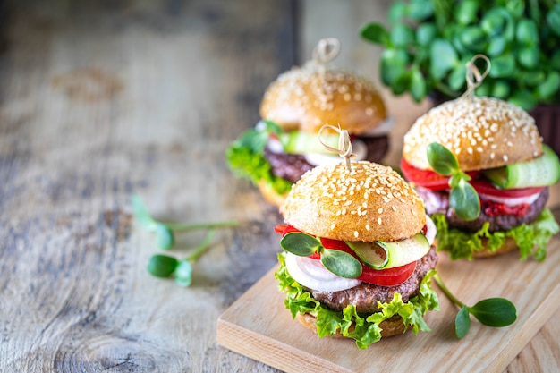 Zelfgemaakte hamburgers met kotelet, verse sla, tomaten, uien op een houten tafel.