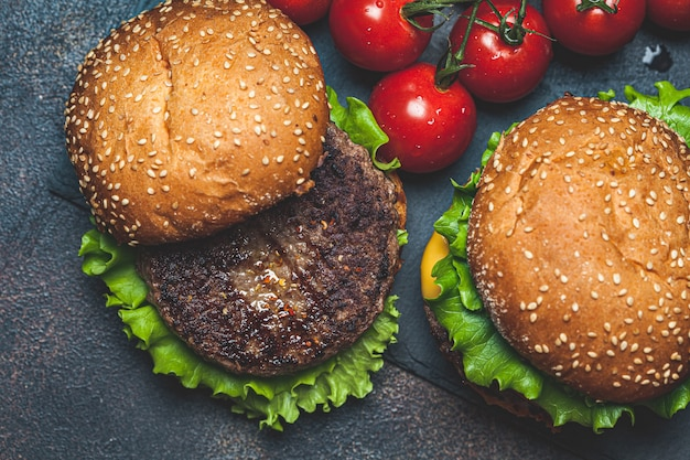 Zelfgemaakte hamburgers met rundvleeskotelet, kaas en groenten, een donkere achtergrond, bovenaanzicht.