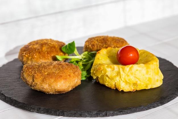 Zelfgemaakte hamburgers of koteletten met gebakken gevormde aardappelen en salade op stenen plaat en houten tafel.