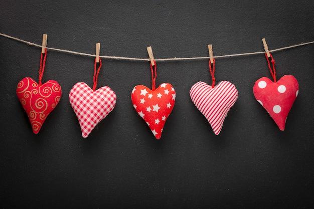 Zelfgemaakte harten aan een touw op een donkere muur. valentines concept