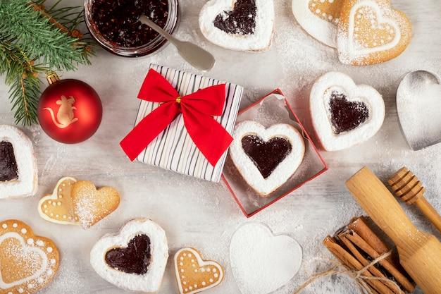 Zelfgemaakte hartvormige koekjes met frambozenjam op witte houten tafel voor kerstmis of valentijnsdag. bovenaanzicht