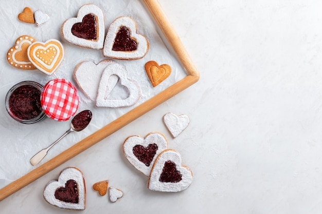 Zelfgemaakte hartvormige koekjes met frambozenjam op witte tafel voor kerstmis of valentijnsdag. bovenaanzicht.