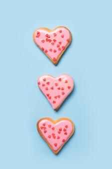 Zelfgemaakte hartvormige koekjes op witte tafel.