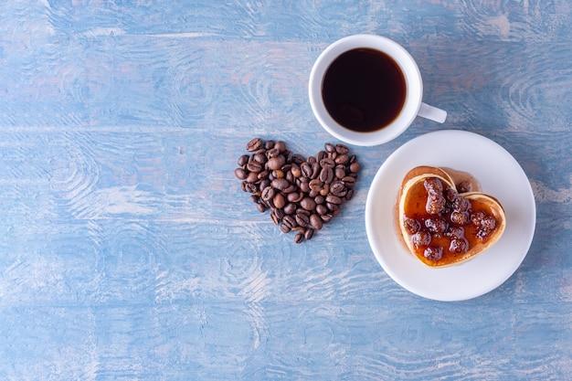 Zelfgemaakte hartvormige pannenkoeken met bessenjam, hartvorm gemaakt van koffiebonen en een witte kop warme koffie op een blauwe houten tafel