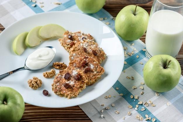 Zelfgemaakte haver pannenkoeken met veganistische yoghurt, rozijnen en walnoot op de houten tafel met blauwe stof in de doos.
