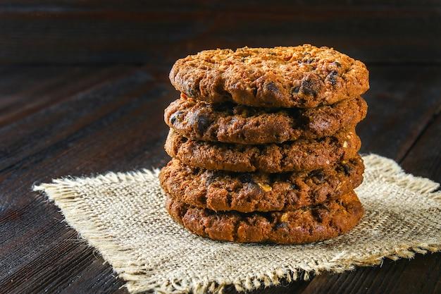 Zelfgemaakte havermout koekjes. een stapel jute op een bruine houten tafel.