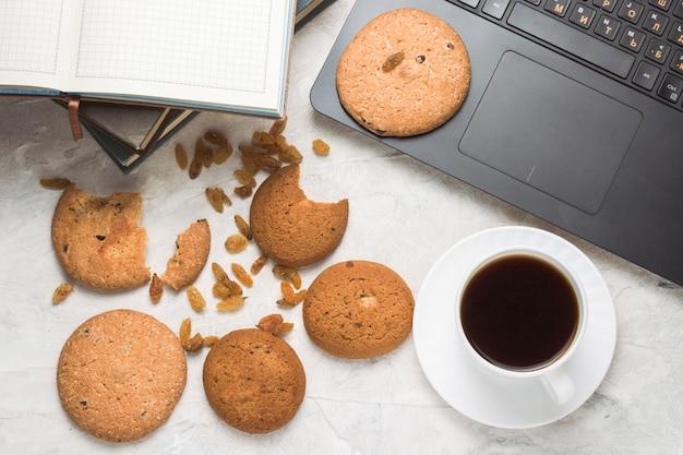 Zelfgemaakte havermout koekjes, kopje koffie, boeken en laptop op een licht stenen oppervlak. concept van onderwijs