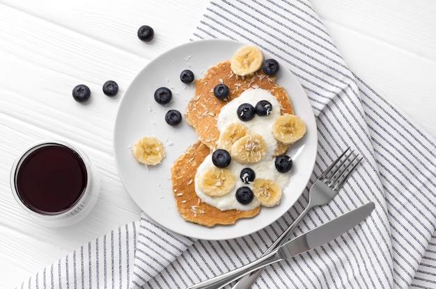 Zelfgemaakte havermout pannenkoeken met yoghurt, verse bosbessen en bananen op witte houten tafel.