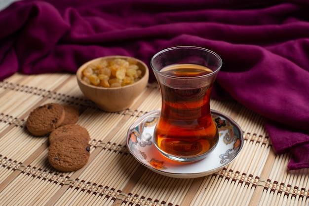 Zelfgemaakte havermoutkoekjes met een kopje turkse thee en een kom rozijnen