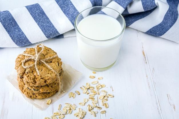 Zelfgemaakte havermoutkoekjes met rozijnen en chocolade en glas melk op witte lijst