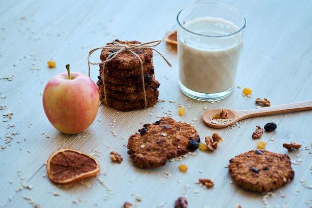Zelfgemaakte havermoutkoekjes met walnoot, rozijnen en melk op een houten tafel