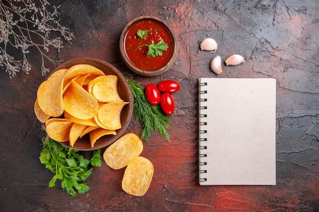 Zelfgemaakte heerlijke aardappelkrokante chips in een kleine bruine kom oliefles groene tomaten knoflookketchup en notitieboekje op donkere tafel