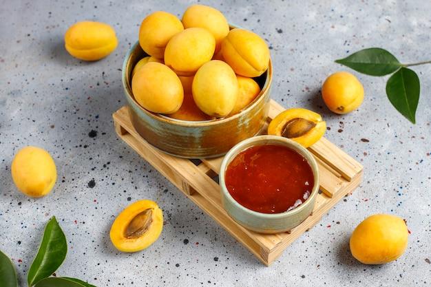 Zelfgemaakte heerlijke abrikozenjam met verse abrikozenvruchten.