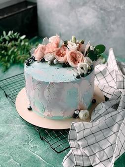 Zelfgemaakte heerlijke en sappige cake versierd met blauwe room en verse bloemen op blauwe achtergrond