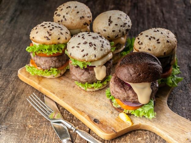 Zelfgemaakte heerlijke gegrilde hamburgers met rundvlees, tomaten, kaas, zoete uien en een groene salade op hout