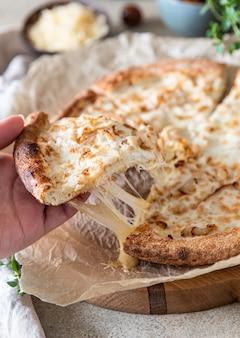 Zelfgemaakte heerlijke hete pizza met kip en plak met smeltende strekkaas