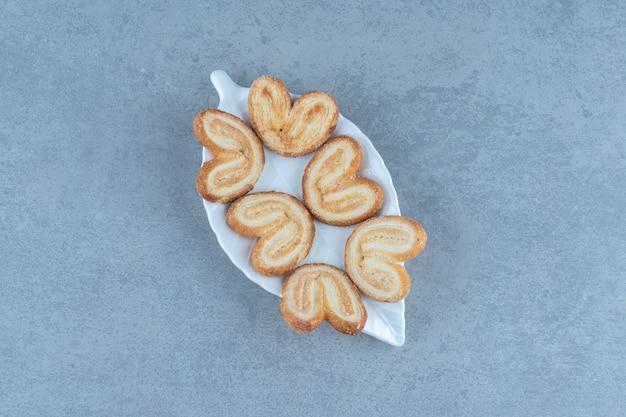 Zelfgemaakte heerlijke koekjes op witte plaat over grijze tafel.