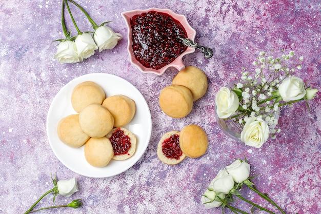 Zelfgemaakte heerlijke koekjes serveren met frambozenjam, bovenaanzicht