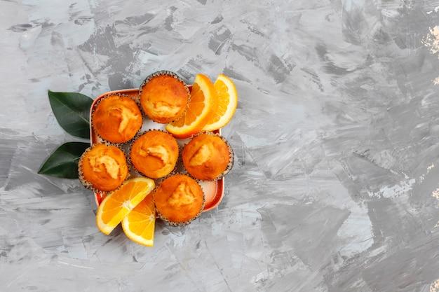 Zelfgemaakte heerlijke oranje muffins met verse sinaasappelen.