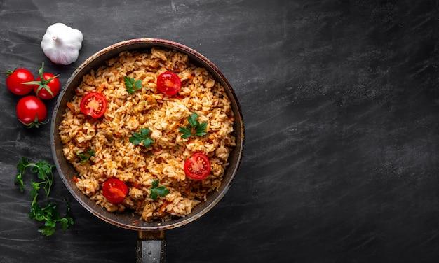 Zelfgemaakte heerlijke pilaf met kip, verse peterselie en rijpe groenten in een pan voor de lunch