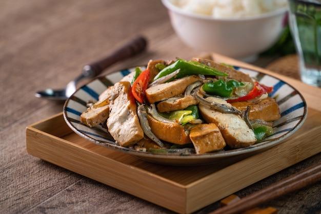 Zelfgemaakte heerlijke roergebakken gedroogde tahoe met gedroogde vis en groene chili op houten tafel achtergrond.
