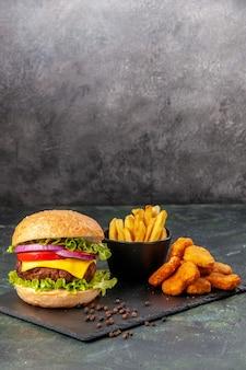 Zelfgemaakte heerlijke sandwich frietjes kipnuggets op zwarte bord frietjes peper op donkergrijs wazig oppervlak