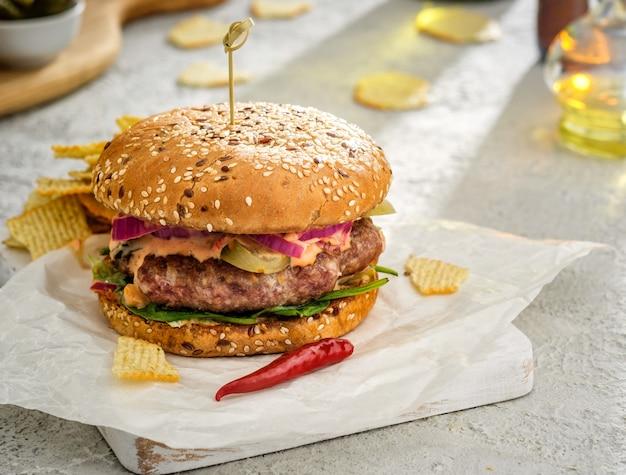 Zelfgemaakte heerlijke sappige burgerburger met rode uienringen, ingelegde komkommers en saus.