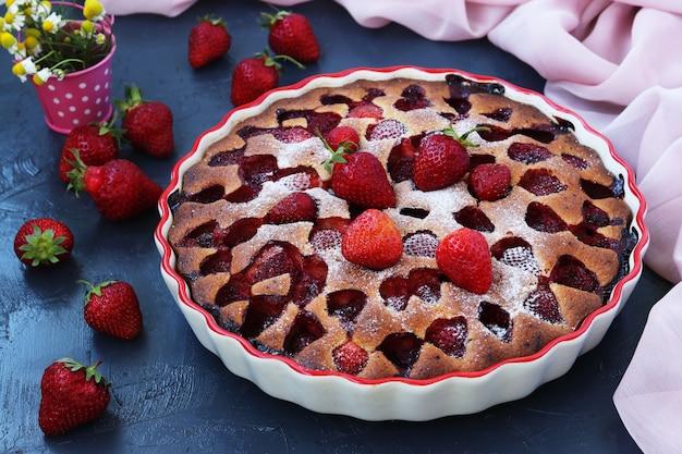 Zelfgemaakte heerlijke taart met aardbeien in keramische vorm op een donkere ondergrond. detailopname