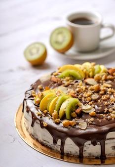 Zelfgemaakte heerlijke zoete cake met fruit, chocolade, appel, kiwi op kopje koffie americano