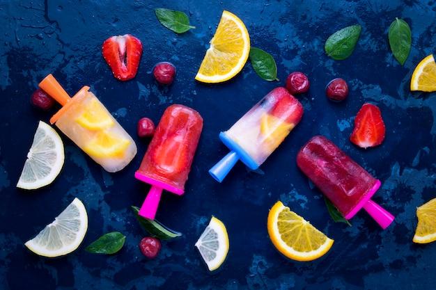 Zelfgemaakte heldere fruitijslolly met aardbei, kers, citroen, sinaasappel, citroen en muntsmaak en vers fruit voor ijs op een donkerblauw
