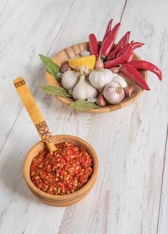 Zelfgemaakte hete adjika van hete pepers met kruiden op een witte houten tafel.