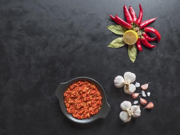 Zelfgemaakte hete adjika van hete pepers met kruiden op een zwarte tafel achtergrond