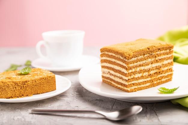 Zelfgemaakte honingcake met melkroom en munt met een kopje koffie op een en roze oppervlak en groen textiel