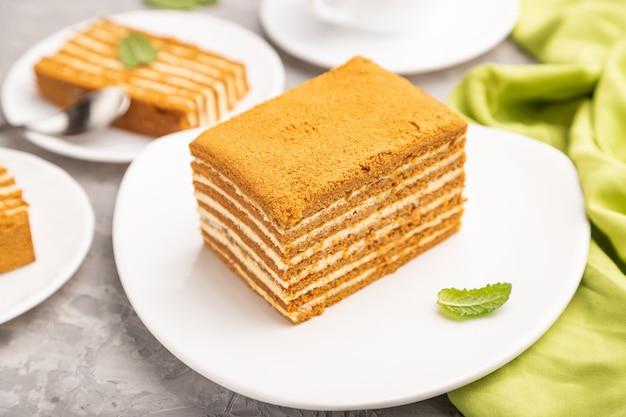Zelfgemaakte honingcake met melkroom en munt met kopje koffie op een grijze betonnen tafel en groen textiel. zijaanzicht, close-up.