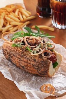 Zelfgemaakte hotdog met rucola en uien frietjes