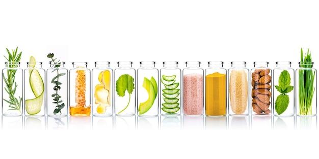Zelfgemaakte huidverzorging en bodyscrubs met natuurlijke ingrediënten in glazen flessen isoleren op witte achtergrond.