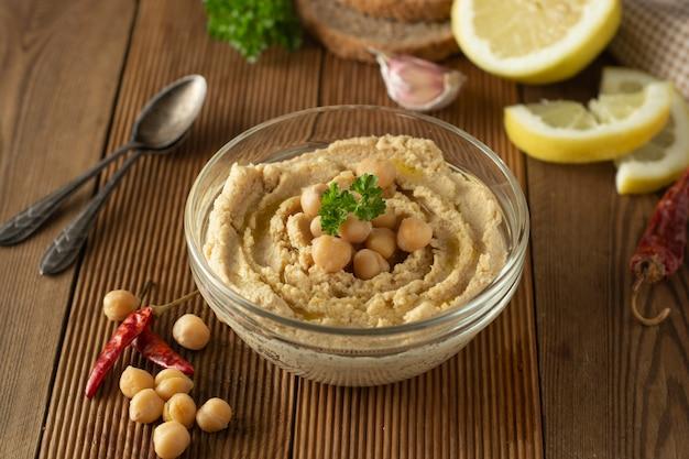 Zelfgemaakte hummus. vrouwenhanden met hummus in kom, olijfolie, citroen en kruiden.
