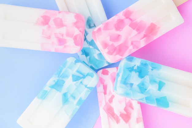 Zelfgemaakte ijs sticks, ijslolly, ijs pop of vriezer pop op blauwe en roze pastel kleuren achtergrond